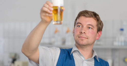 OeTTINGER-Mitarbeiter begutachtet ein Bier