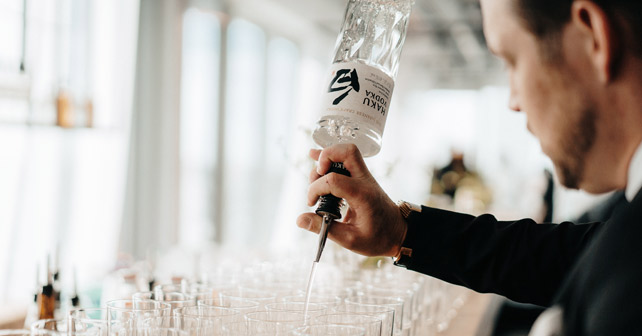 Mann schenkt Haku Vodka ein
