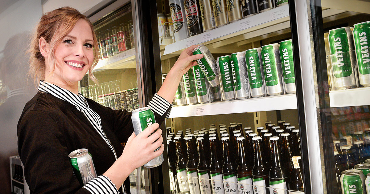 Frau stellt Veltins Dosen in Regal