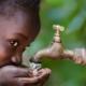 Mädchen trinkt Wasser aus Wasserhahn