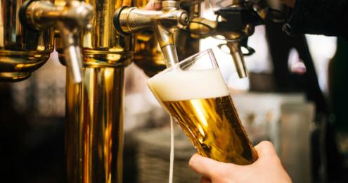mann zapft ein bier am zapfhahn