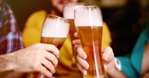 drei männer stoßen mit einem bier an