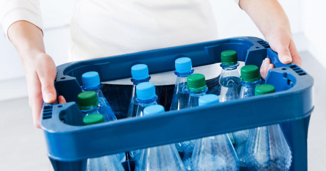 hände einer frau mit einem kasten mineralwasser
