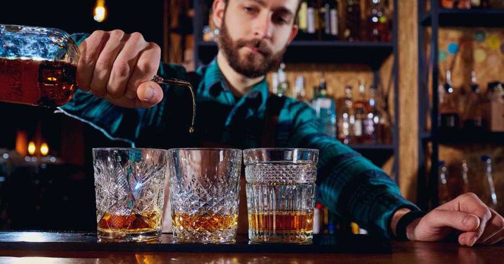 barman pours alcohol into a glass
