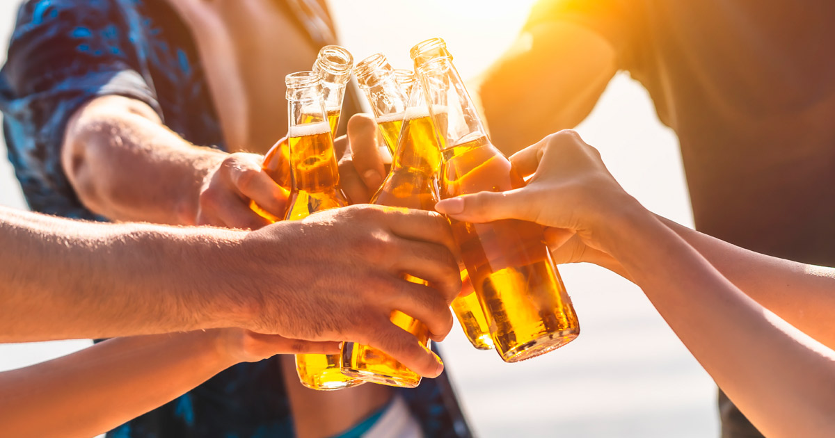 The hands holding bottles with beer and making cheers