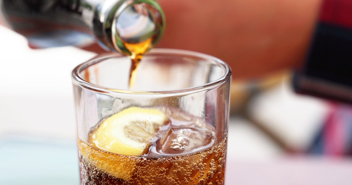 Hand pouring cola soda drink from bottle to glass with ice cubes and lemon slices