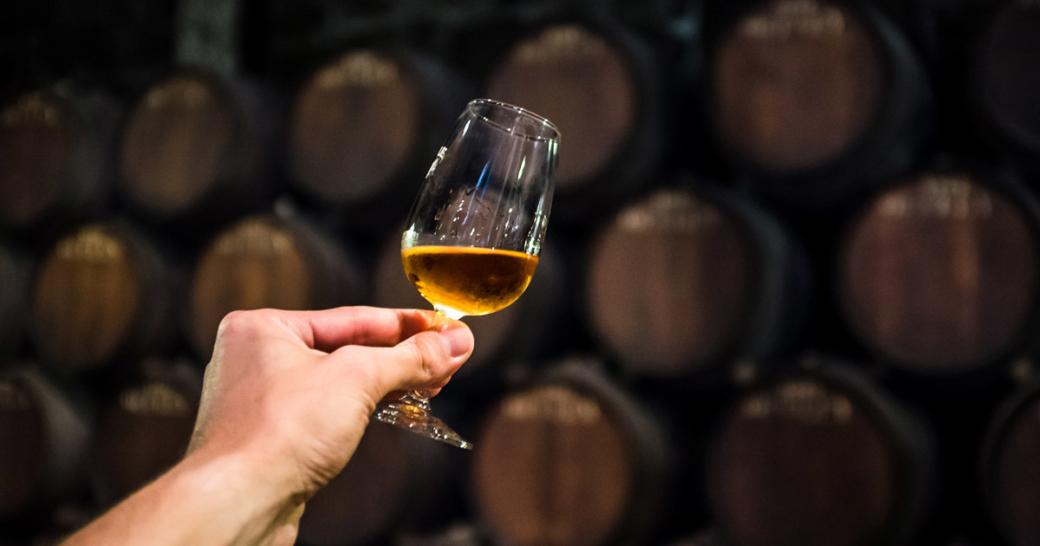 port wine in wine cellar, glass of alcohol in cellar, glass of wine in hand, wine degustation