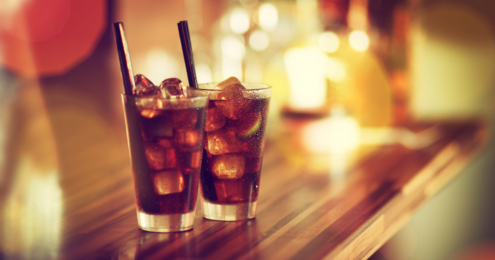 Two glasses of rum-cola cocktail with ice served on the bar